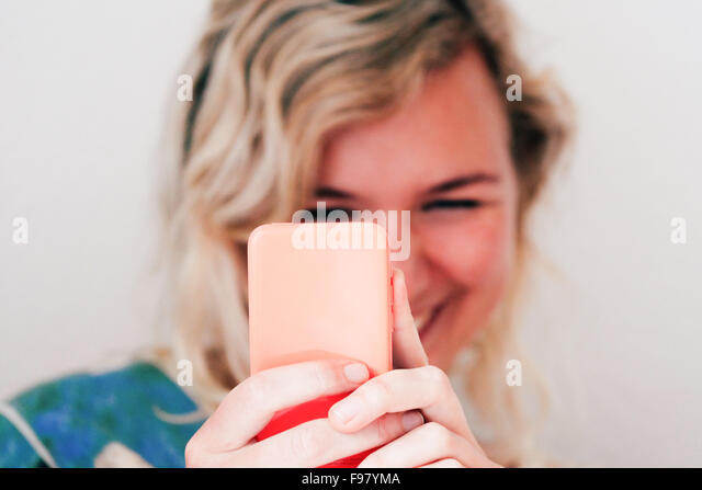 Smiling Young Woman Using Mobile Phone At Home - Stock Image