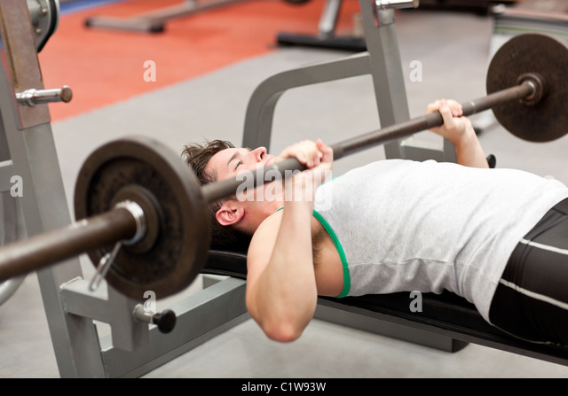 Muscular young man using weightlifting lying in a fitness centre - Stock Image