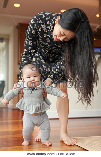 Mother helping baby girl to walk - Stock Image