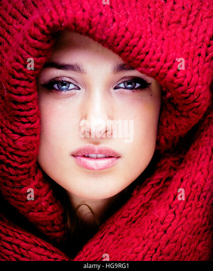young pretty woman in sweater and scarf all over her face, lifestyle winter people concept - Stock Image