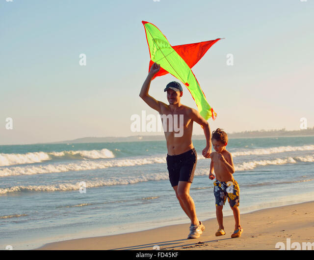 father with son, sunset at the seacoast with kite, happy family - Stock-Bilder