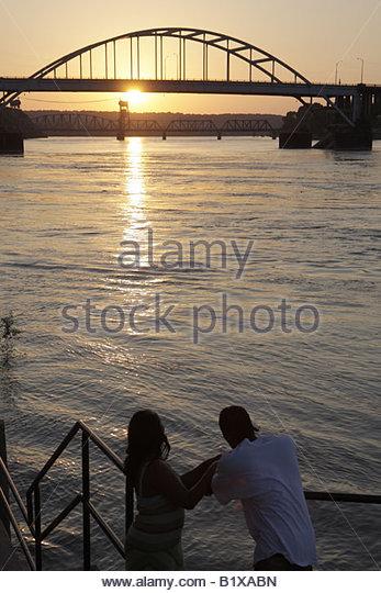 Arkansas Little Rock Arkansas River man woman bridge sunset water reflection - Stock Image