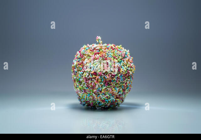 Apple covered in multi-colored sprinkles - Stock Image