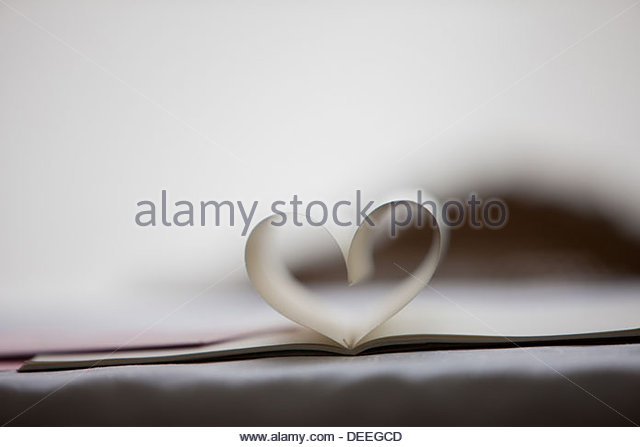 Close up of lipstick kiss on envelope and pages of notebook forming heart-shape - Stock-Bilder