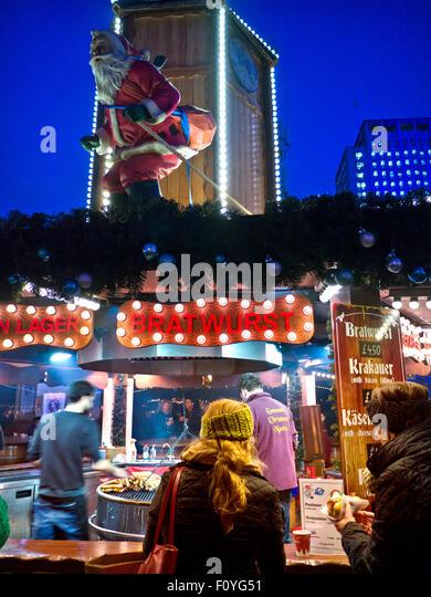 CHRISTMAS SOUTHBANK German Christmas market food stall illuminated at night South Bank London UK - Stock Image