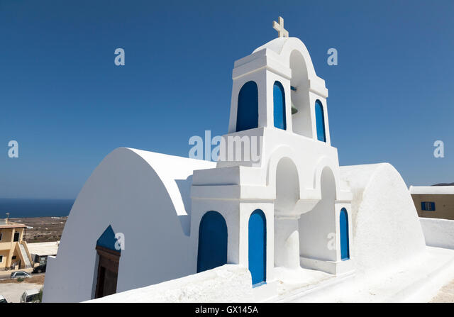A traditional blue and white Christian building in the Greek island of Santorini. The image is set against a clear - Stock Image