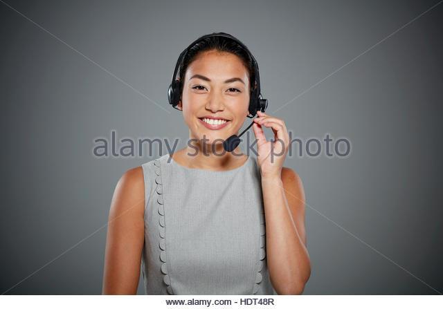 Portrait of young woman wearing headset. - Stock Image