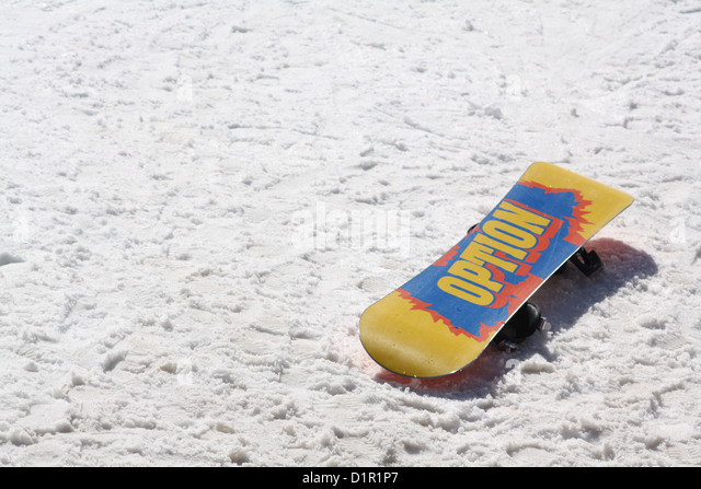 Canary yellow snowboard lies upside down in snow revealing large blue and red Option logo on the underside - Stock Image