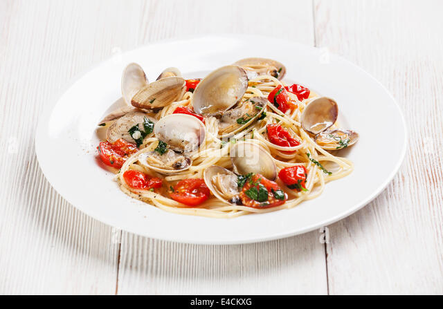 Seafood pasta with clams in tomato sauce Spaghetti alle Vongole on white wooden background - Stock Image