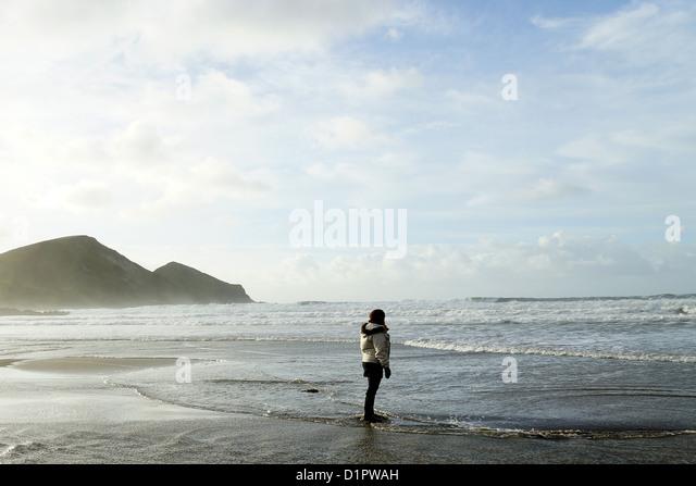 Person on beach, Crackington Haven, Cornwall, UK. - Stock Image