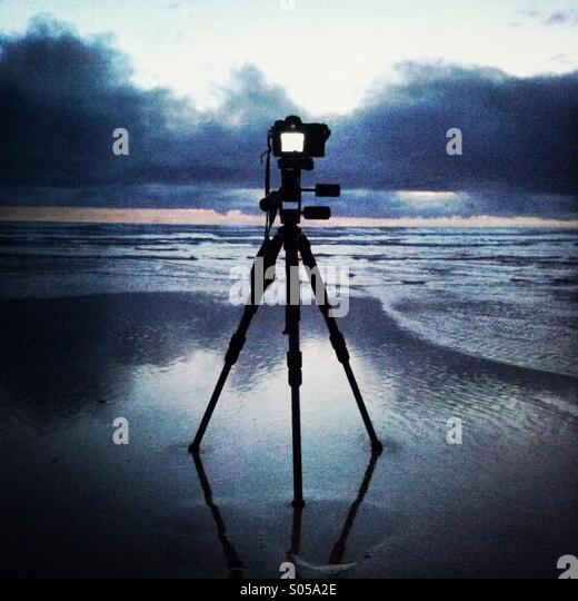A camera on a tripod captures the sunset on the beach at Watergate Bay. Newquay, Cornwal, England UK. - Stock Image