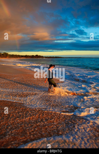 beautiful middle age woman walking on the shore alone on makena beach, maui at sunset - Stock Image
