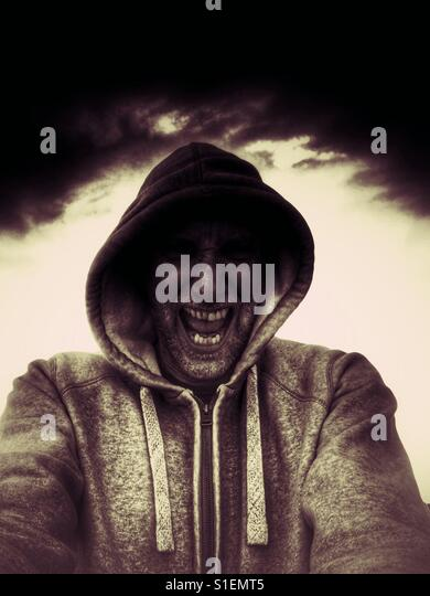 Angry Man in hoodie yelling - Stock Image