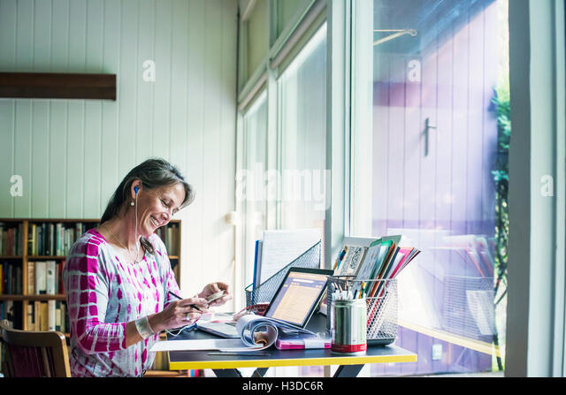 Woman sitting at a desk at home, working. - Stock Image