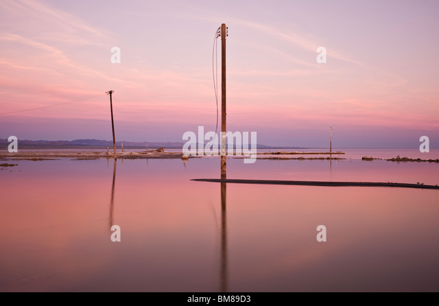 Abandoned telephone poles in water, Bombay Beach, Salton sea, California - Stock Image