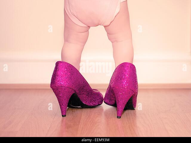 Toddler wearing mother's shoes - Stock Image