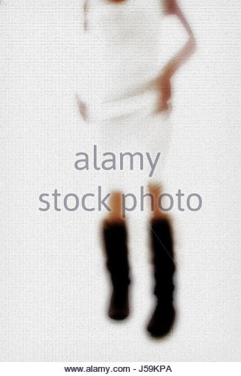 Impressionistic anonymous image of female body in boots and a dress - Stock Image