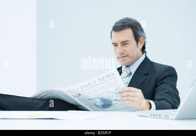 Businessman sitting at desk, reading newspaper, looking down with concerned expression - Stock-Bilder