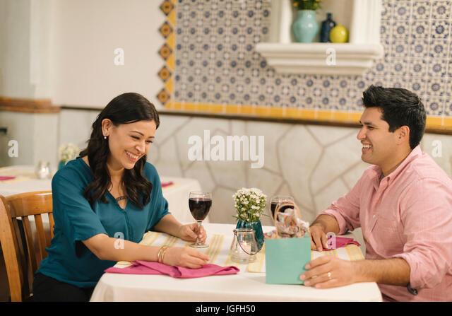 Hispanic couple laughing in restaurant - Stock Image
