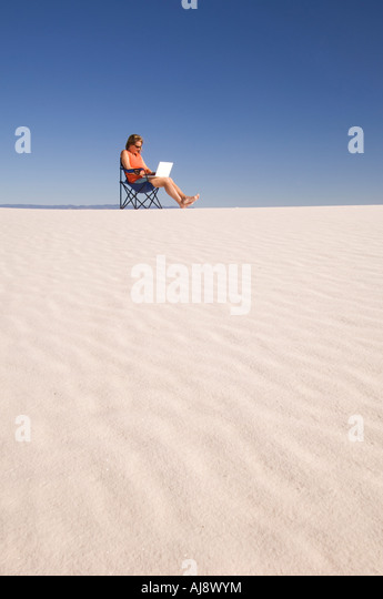 Woman using laptop in the sand dunes. - Stock-Bilder