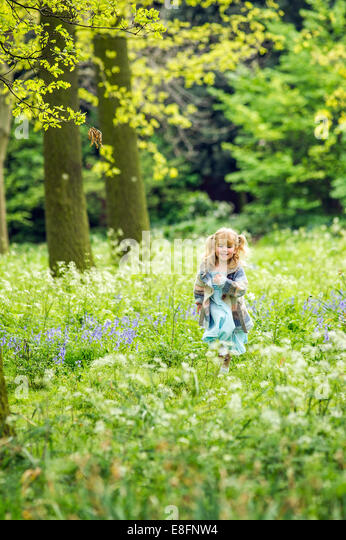UK, Warwickshire, Rugby, Girl (4-5) running in woods - Stock Image