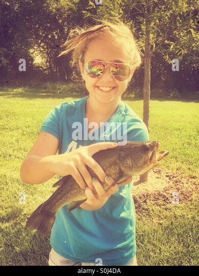 Young girl holding a Largemouth Bass she caught while fishing - Stock Image