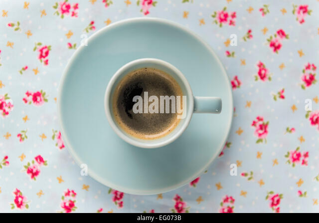 Espresso coffee in a blue cup and saucer on a floral table cloth. - Stock Image