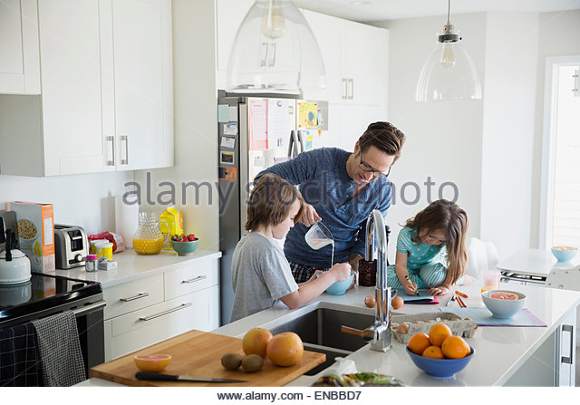 Father pouring milk for son in breakfast kitchen - Stock Image