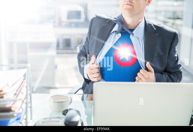 Businessman opening shirt to reveal superhero costume - Stock Image