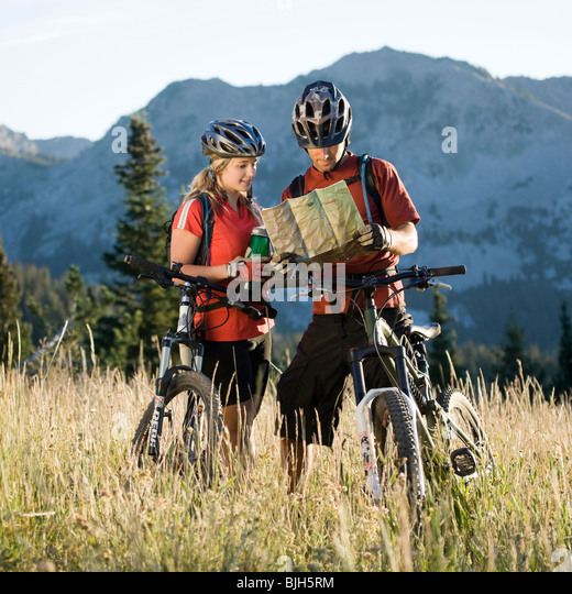 mountain bikers looking at a map - Stock Image