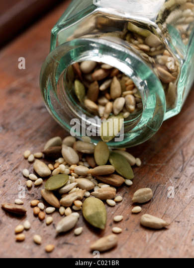 Glass bottle with various seeds - Stock Image