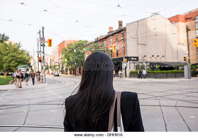 Rear view of woman standing in Toronto street - Stock Image