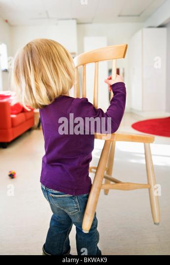 Girl carrying chair - Stock-Bilder