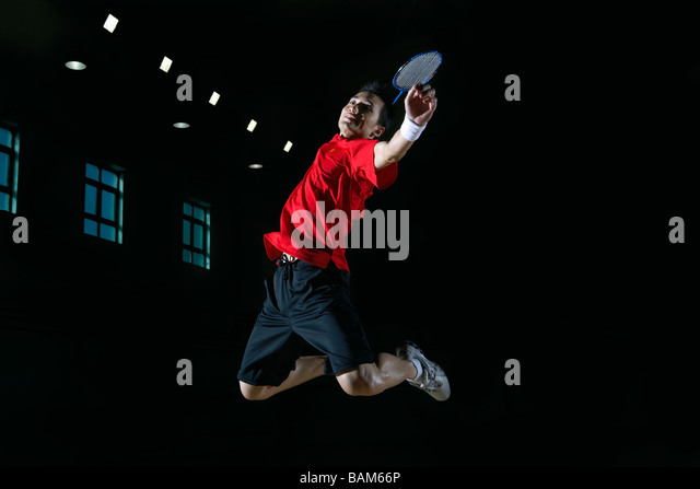 Young Man Leaps High In The Air During A Game Of Badminton - Stock Image