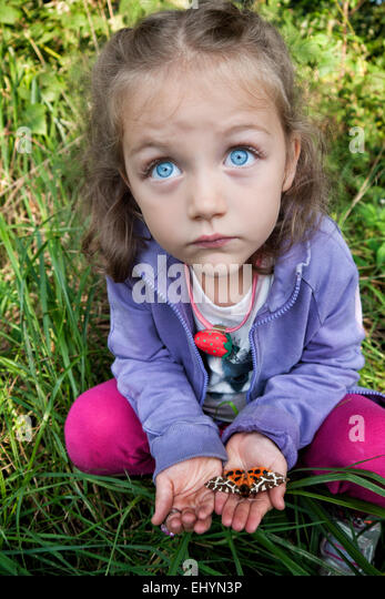 Girl holding a moth in the palm of her hands - Stock Image