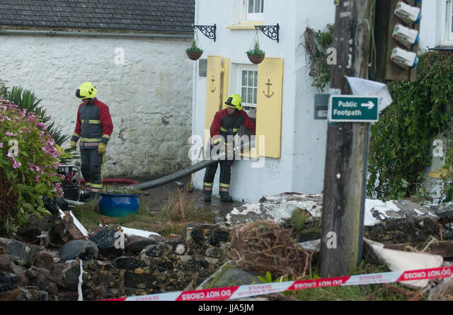 Coverack, Cornwall. 18th July 2017.  Cornwall Fire and Rescue pump Local house after Flash flood in coastal village - Stock Image