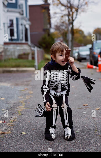 Smiling boy (2-3) in skeleton costume holding chocolate bar - Stock Image
