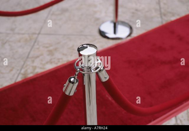 Velvet ropes and red carpet on sidewalk for awards ceremony. 'Red Carpet' treatment. - Stock Image