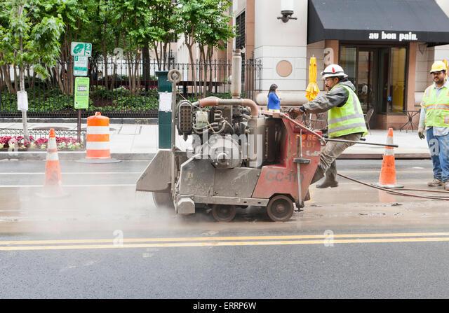 Municipal construction workers using walk behind asphalt saw, Diamond Core Cut machine - USA - Stock-Bilder