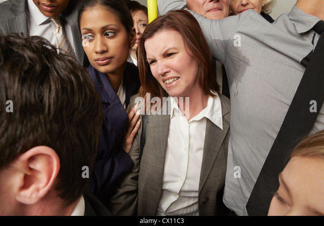 Woman and man with sweaty armpit on crowded subway train - Stock Image