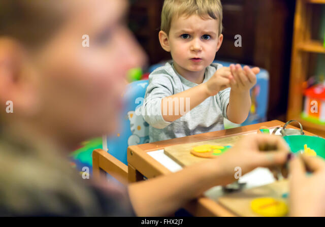 Little boy being creative with playdough - Stock Image