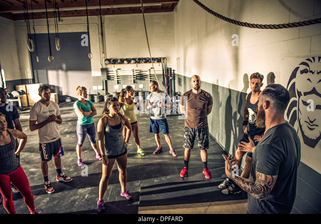 Trainer talking to fitness class in gym - Stock Image