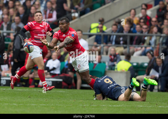 A player under pressure gets the ball away despite being tackled in the 100th fixture of the Army v Navy rugby match - Stock Image