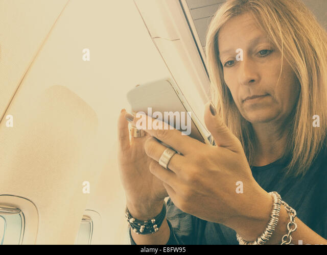 Businesswoman on airplane using smartphone - Stock-Bilder