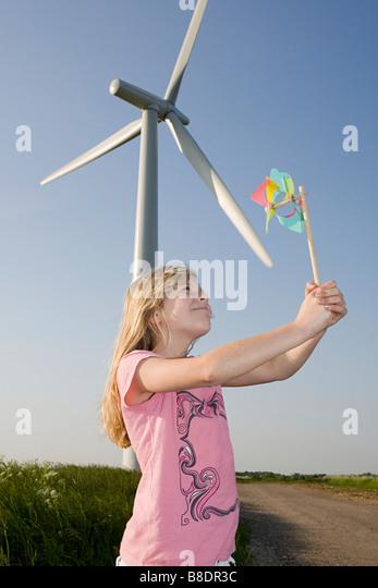 Girl with pinwheel by wind turbine - Stock Image