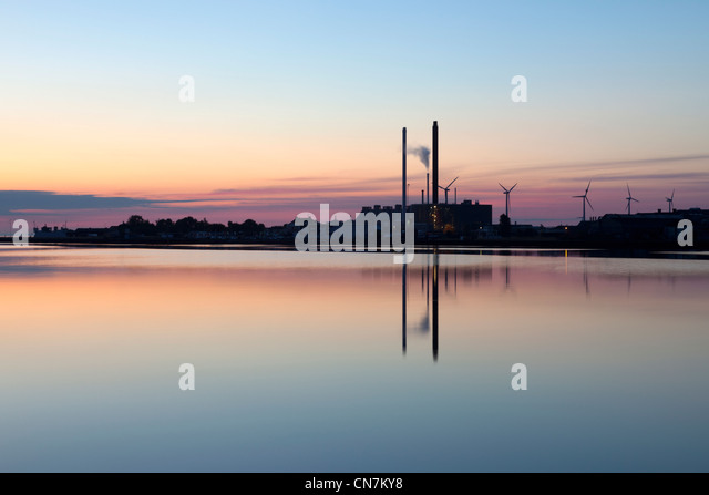 Smokestacks reflected in water - Stock Image