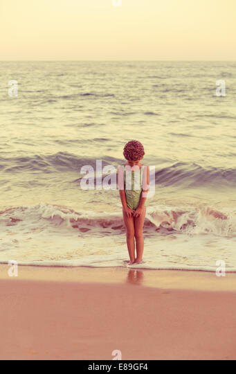 Girl in swimcap standing in the waves - Stock-Bilder
