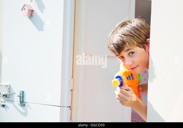 Boy holding water pistol and peering out of caravan, portrait - Stock Image