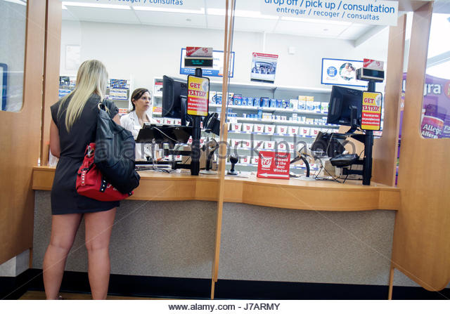 Miami Beach Florida Walgreen's pharmacy drugstore woman women pharmacist customer counter pick-up - Stock Image