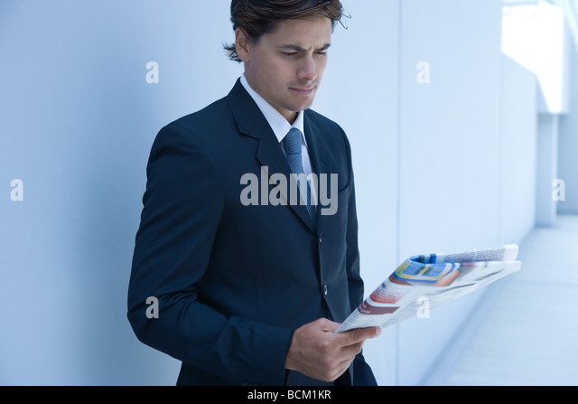 Businessman standing, reading newspaper - Stock Image